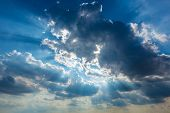 Dramatic cloudy sky clouds with real sun beams background