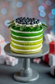stock photo of cake stand  - Nice sponge happy birthday cake with mascarpone and grapes with on the cake stand with gift boxes on festive light bokeh background - JPG