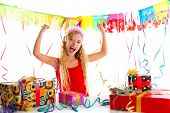 Party blond kid girl happy with many presents hands up excited