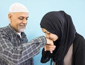 Arabic Muslim girl with her father kissing his hand for respect