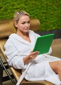 people, beauty, lifestyle, technology and relaxation concept - beautiful young woman in white bath robe with tablet pc computer social networking at spa