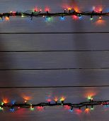 Colorful Christmas lights on wooden planks background