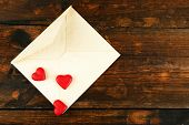 Empty envelope with hearts on rustic wooden table background