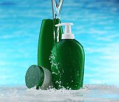 Cosmetic products in water splashes on blue background