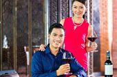 Portrait of Asian couple with a glass of red wine