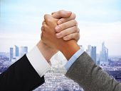 business competition, challenge, cooperation, people and partnership concept - concept - close up of hands arm wrestling over city background