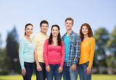 friendship, summer vacation, nature and people concept - group of smiling teenagers standing over green park background