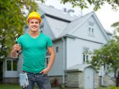 repair, construction, people, building and maintenance concept - smiling male manual worker in protective helmet holding hammer over house background