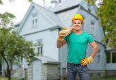 repair, construction, people, building and maintenance concept - smiling male manual worker in protective helmet carrying wooden boards over house background