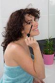 A Woman Applying Mascara Makeup On Eyes By Brush