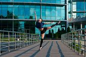 Ballerina dancing in casual clothes standing on tiptoes. Acrobatics, ballet, dance. Outdoor