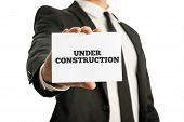 Businessman In A Suit Holding Up A Business Card Saying Under Construction