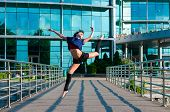 Ballerina dancing in casual clothes jumping on tiptoes. Acrobatics, ballet, dance. Outdoor
