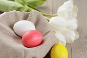 easter eggs and white tulips on wood table