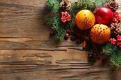 Fruits with nuts, spices and sprigs of Christmas tree on rustic wooden background