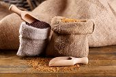 Mustard seeds in bags on  wooden background