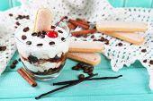 Tasty tiramisu dessert in glass, on color wooden background