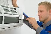 picture of air conditioner  - Portrait Of Young Male Technician Repairing Air Conditioner - JPG