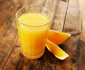 Glass of orange juice with slices on wooden table background
