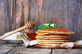 Stack of pancakes with honey and butter on rustic wooden background