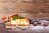 Cheese cake with sugar powder on paper on wooden table on wooden wall background
