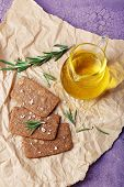 Crispbread with salt, jug of oil and sprigs of rosemary on crumpled piece of paper and color wooden background