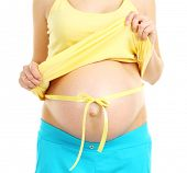 Beautiful young pregnant woman with measuring tape on her belly isolated on white