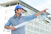 Confident male architect with blueprint pointing away while standing outside building