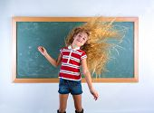 funny student girl flipping long blond hair at school classroom chalk board