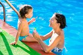 Baby girl blowing soap balloons with mother in swimming pool at summer vacation