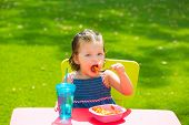 Toddler kid girl eating macaroni tomato pasta in garden turf grass