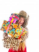 Blond winter kid girl with stacked presents smiling happy with fur hat