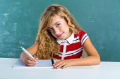 Blond student girl writing notebook at class green chalk board sitting in desk