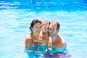 Happy family in swimming pool with baby girl in summer vacation