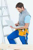 Portrait of carpenter using laptop over white background