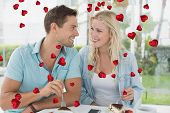 Hip young couple having desert together against valentines heart design