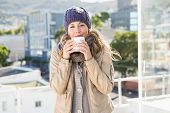 Pretty blonde in warm clothes drinking hot beverage in the city