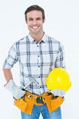 Portrait of happy handyman holding hammer and hard hat over white background