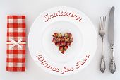 Invitation to dinner for two. Valentine's Day table setting with heart of roses on a plate.