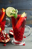 Pomegranate drink in glasses with mint and slices of orange and lime on color wooden background