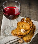 glass of red wine with nuts and crackers