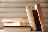 Stack of books on wooden planks background