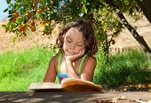 little girl reading under a tree, portrait