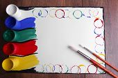 Colorful paint strokes on sheet of paper and wooden table background