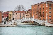 Tourists Crossing Water Canal In Venice