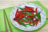 Decorative Composition With Chili Pepper On A Plate And Chopsticks.