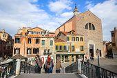 Tourists Walking Over Bridge In Venice