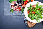 Sliced prosciutto with salad and olive