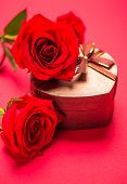 Heart shape gift box with red roses on red background. Valentine's Day gift.