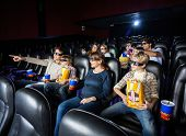 Families having snacks while watching 3D movie in cinema theater